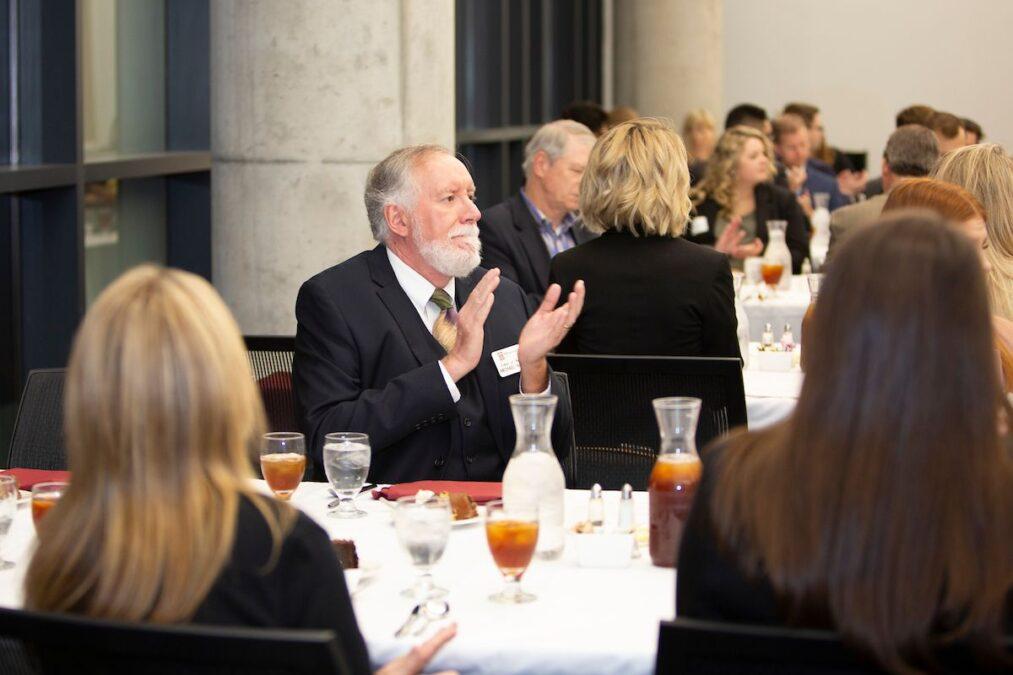 Michael Hammond clapping at an award banquet.