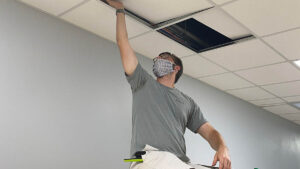 Student lifting ceiling tile.