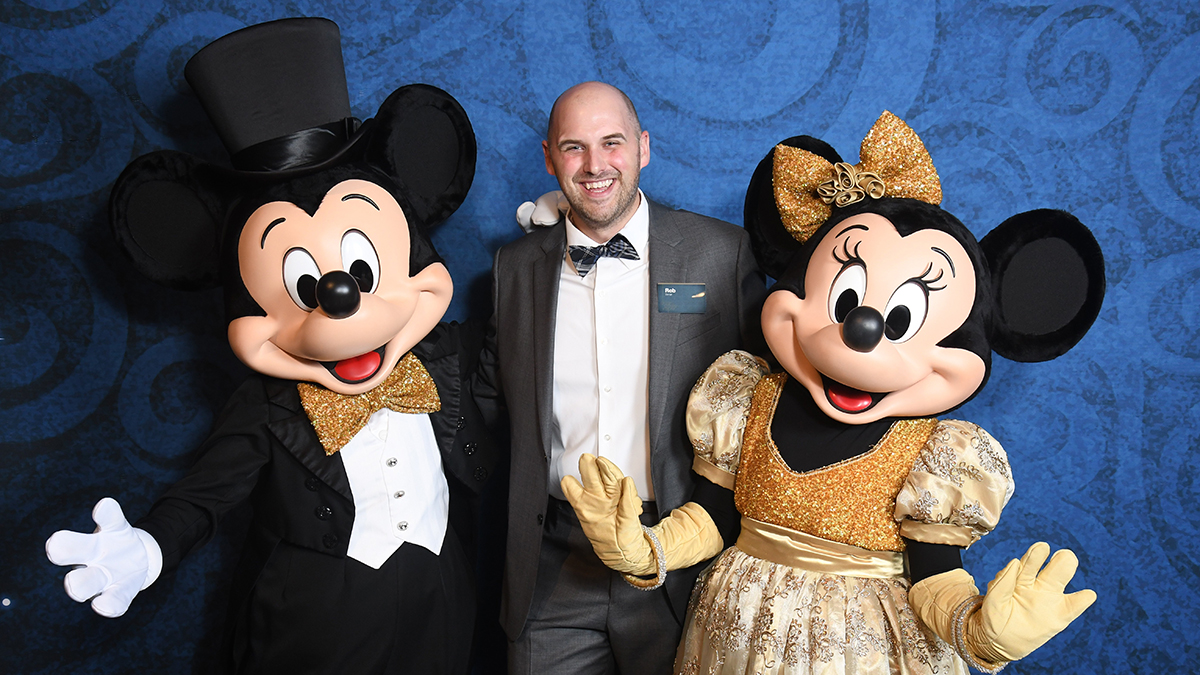 Man in a suit in between Mickey and Minnie Mouse.