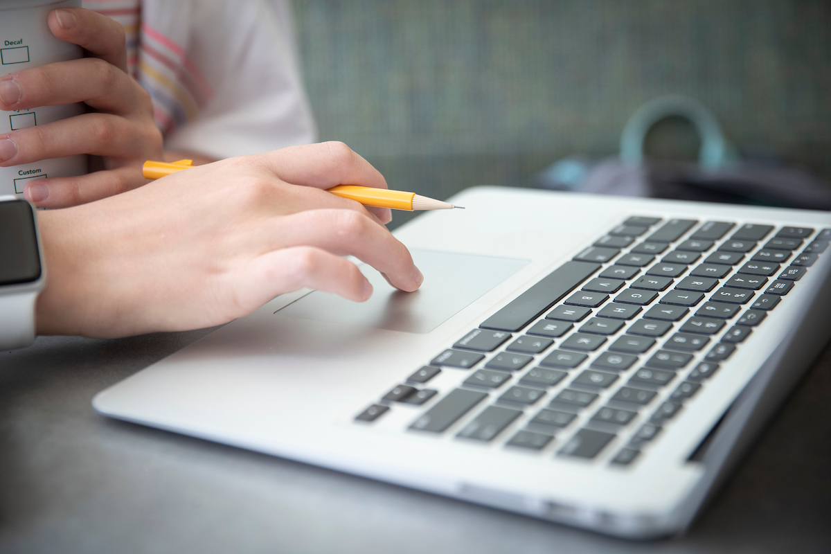 Close up photo of person using laptop keyboard.
