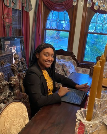 Girl sitting at dining room table with a laptop.