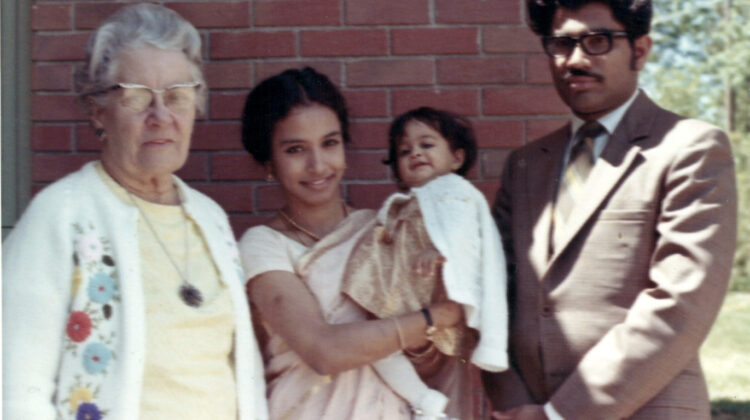 A woman, a woman holding a baby, and a man.