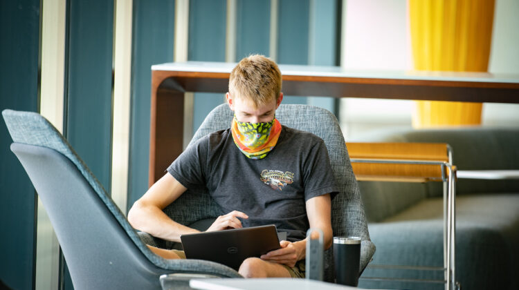 A student with a mask looking at a laptop.