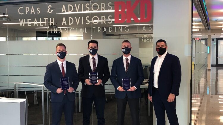 Four men with masks holding award plaques