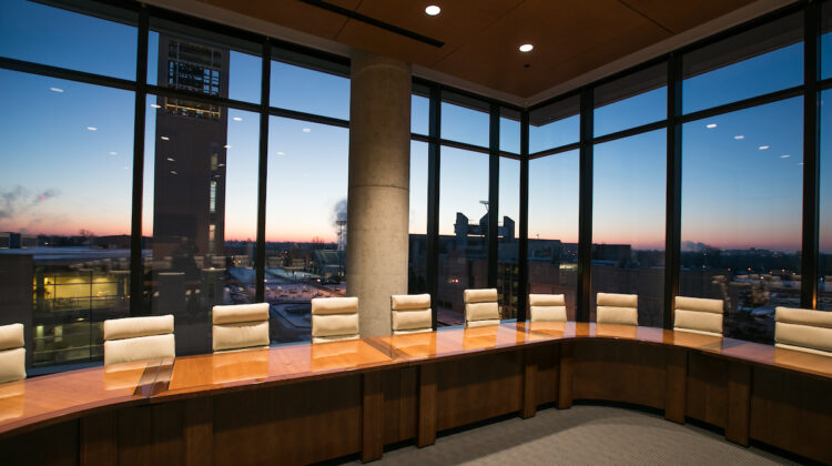 Advisory boardroom at sunrise overlooking campus and bell tower.