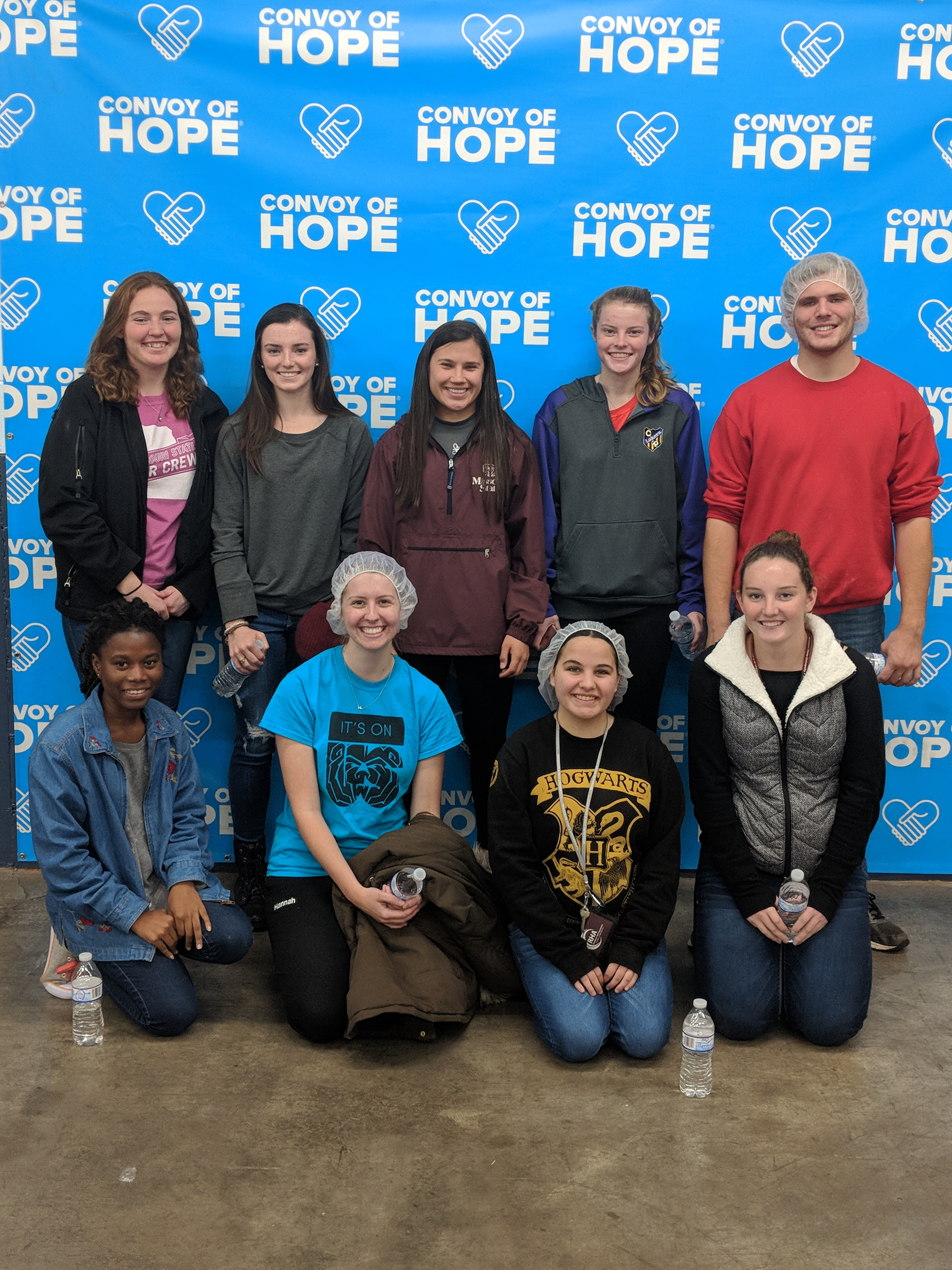 Members of the Bear Service Team pose in front of a Convoy of Hope backdrop