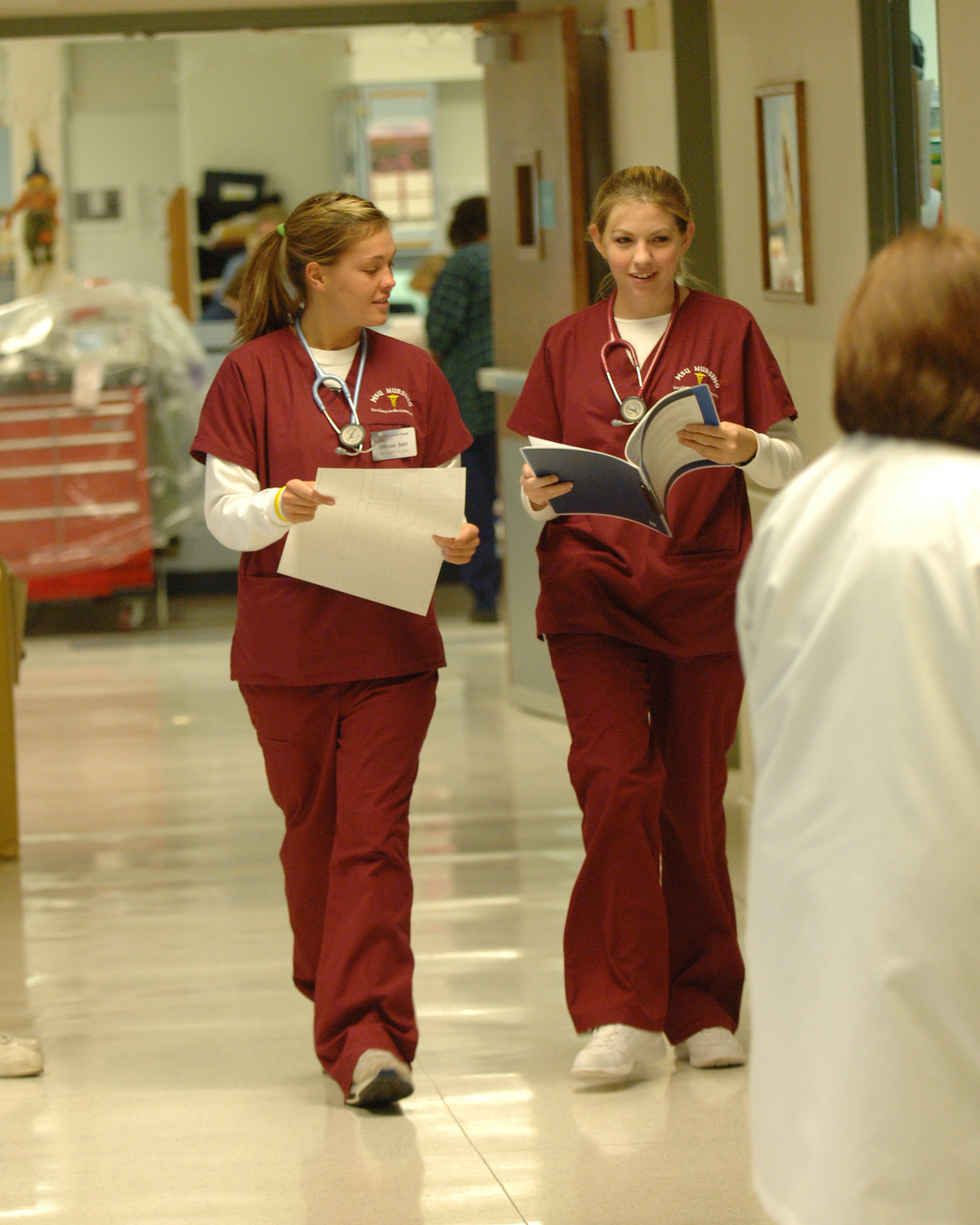 Nursing students in scrubs walk down a clinical hallway together
