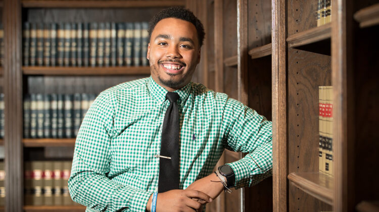 MSU Student Brandon Hill stands in private library with legal texts