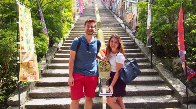 Doctor Marijana and her husband stand at the foot of Japanese shrine's outdoors footsteps