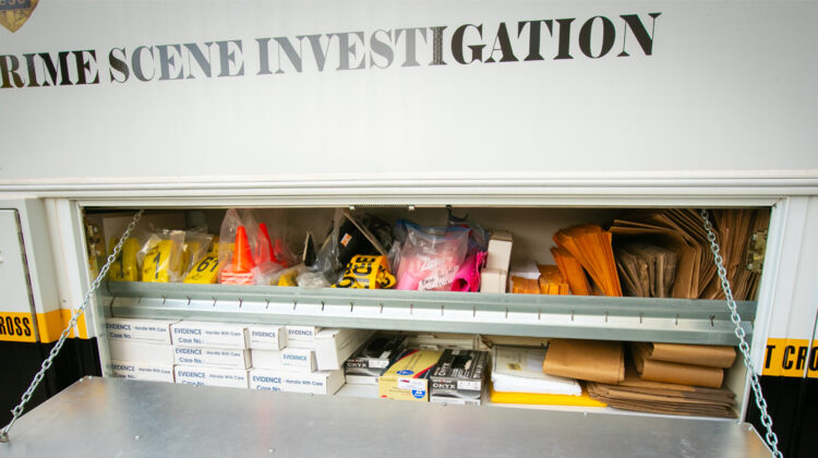 The side door to a police vehicle reveals tagging, marking, and forensic tools for crime scene investigation.