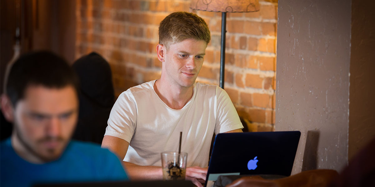 Student works on class online at a coffee shop.