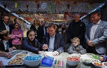 People around a table for Shmini Atzeret/Simchat Torah celebration