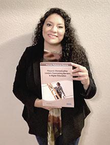 Dr. Daisy Barrón holding her book