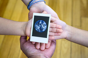 Four hands hold an image of earth on International Mother Earth Day (22 April)