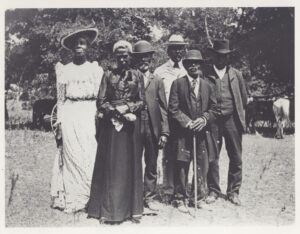 Six African American people dressed up, posing for a photo on Emancipation Day in 1900.
