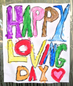 A posted with the words Happy Loving Day and a heart with each letter colored in a different color.