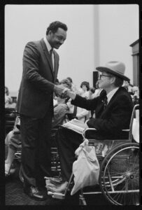 Jesse Jackson shaking hands with disability advocate Justin Dart Jr., who is in a wheelchair, during a hearing of the House Committee on Education and Labor on a bill which became the Americans with Disabilities Act