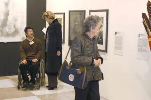 Aman in a wheelchair talking with a woman standing next to him while another woman is looking at the artwork on the wall at an art exhibit showing work by people with disabilities.