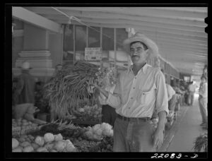 A man standing outside a Mexican market holding vegetables in Brownsville, Texas.