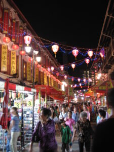 Mid-Autumn Festival in Singapore. People walking down a narrow street with shops on each side and hanging lights above.