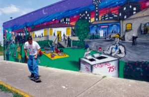Skate board rider in front of a colorful mural, San Antonio, Texas. Mural portrays a man selling raspas (snow cones) in front of lawn and buildings depicted at night.