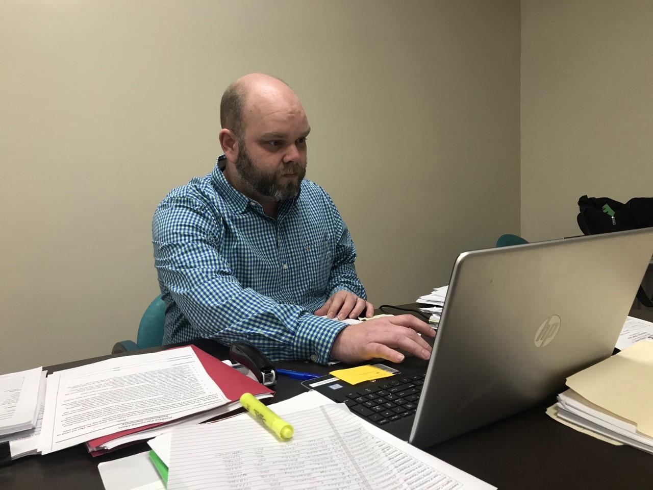 Eli Jones works on his parenting program at his desk.