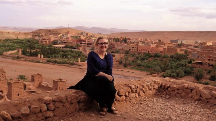 Dr. Jennice McCafferty-Wright sits in front of architecture in Morocco.