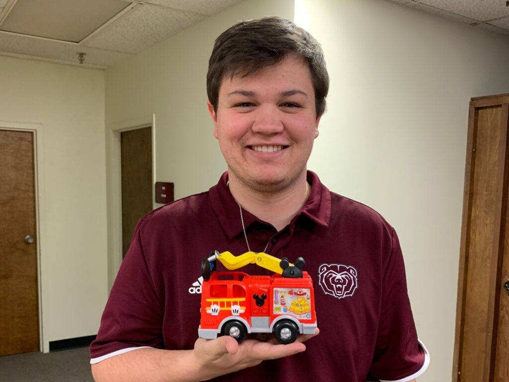 John Augustine holds a toy firetruck for students at the clinic.