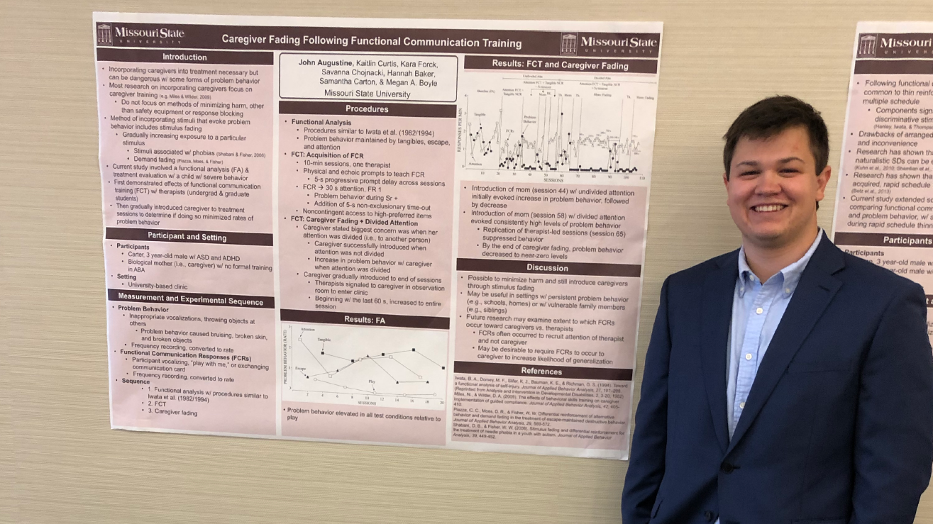 John Augustine stands near his research, displayed on a poster at a recent conference.