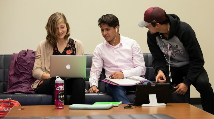 Three students work on an assignment.