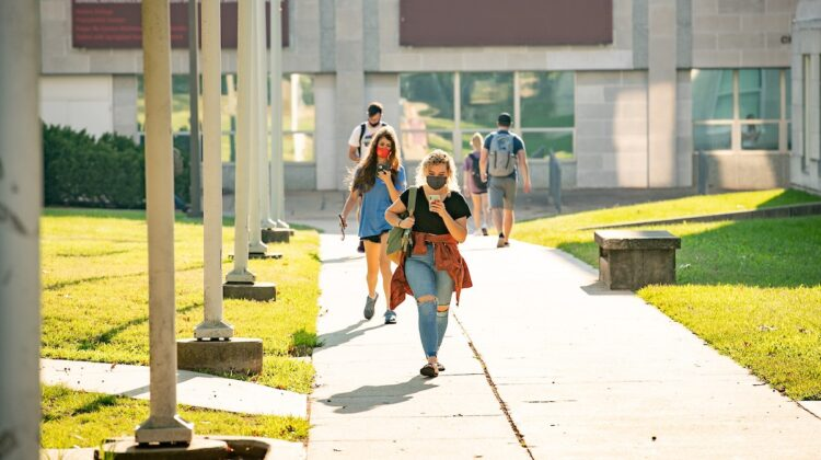 Students walk to their next class on a sunny day.