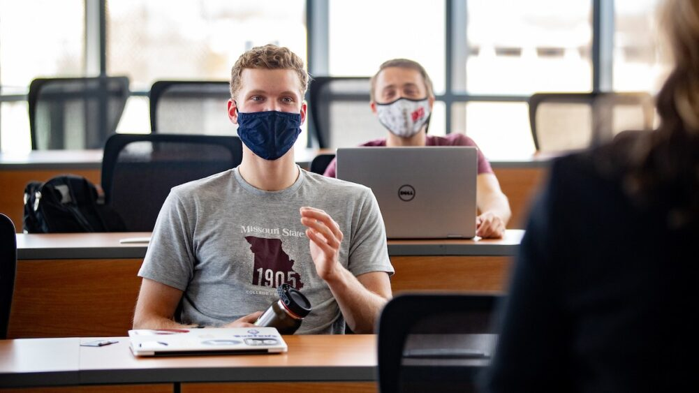 Masked students participate in a class discussion.