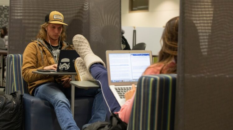 Two students work on their laptops at Meyer Library. One laptop has a Storm Trooper sticker.