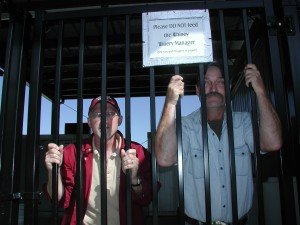 Dr. Karl Wilker (left) and C. J. Odneal (right) peer through the bars of the newly secured and covered outdoor wine processing area.