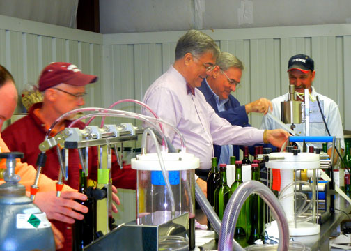 Dr. Cofer (middle left)  is labeling the newly bottled wines while Dr. Anson Elliott (middle right) applies the capsules to the top of the bottles.