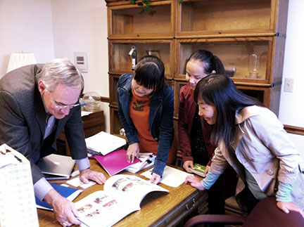 Dr. Elliott (left) looks through the Ningxia Forestry Institute book with Rong, Chunling and Jia (right).