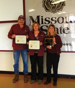 Randy, Susanne (middle) and Pam hold up their service award plaques they received from President Smart.