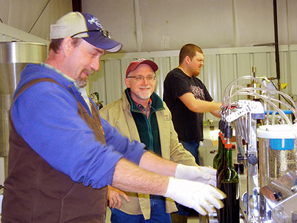 C. J. Odneal, Dr. Karl Wilker, and Josh Glasson make up the bottling line.