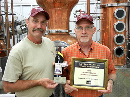 C. J. Odneal (left) and Dr. Karl Wilker (right) hold up the awards won for the Missouri State Maroon Blend Wine.