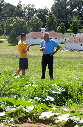Logan Duncan (left) and Dr. Anson Elliott talk about the squash breeding project. Dr. Elliott was trained in classical genetics and worked in a program on the improvement of rice.