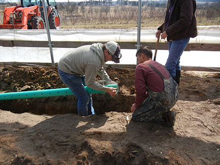 After the trenches were dug, perforated pipe was put in them. The end of the pipe was covered with screen.