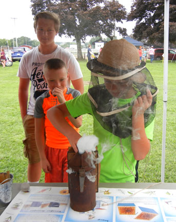A young fellow tries out the bee smoker.