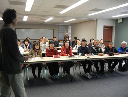 Harold Chung (standing) interprets the lecture about our station and grape growing in Missouri. Professor Kim Jong-Sook is leftmost on the front table.