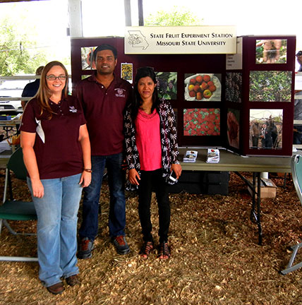 Jennifer Morganthaler, Surya Sapkota and his wife stand in front of our display.