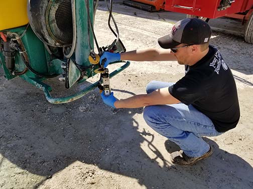 Jeremy Emery checks the output of one of the Cima nozzles with the Spoton calibration tool.