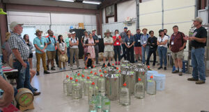 Several carboys of distilled spirits are out for the group to see