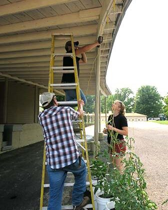 Trace affixes the strings to support the tomato plants while Emily helps line up the locations of the eye bolts. Randy keeps the ladder steady.