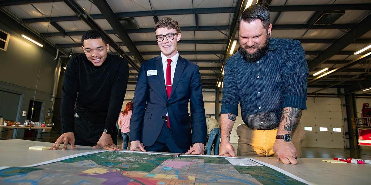Brandon Jenson and Missouri State students look over a map of Willard.