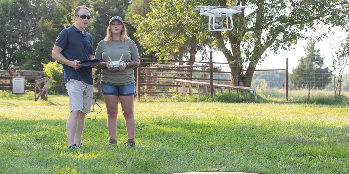 Bailey Wolf watching the drone hover while receiving instructions from Dr. Toby Dogwiler.