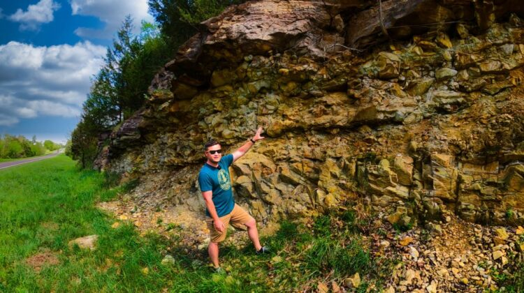 Instructor Damon Bassett poses in front of a rock wall.